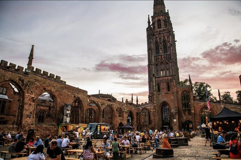 Food market with benches and fairy lit stalls in the ruins of Coventry cathedral on a clear evening