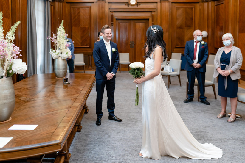 Bride entering ceremony room as groom looks on