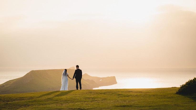 Bride and groom at sunset against the Gower Peninsula