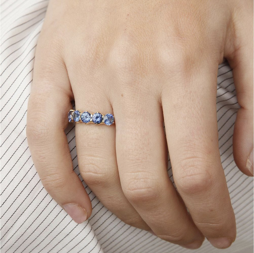 Close-up of woman's hand wearing a five stone light blue sapphire white gold ring against a striped blue and white cloth background