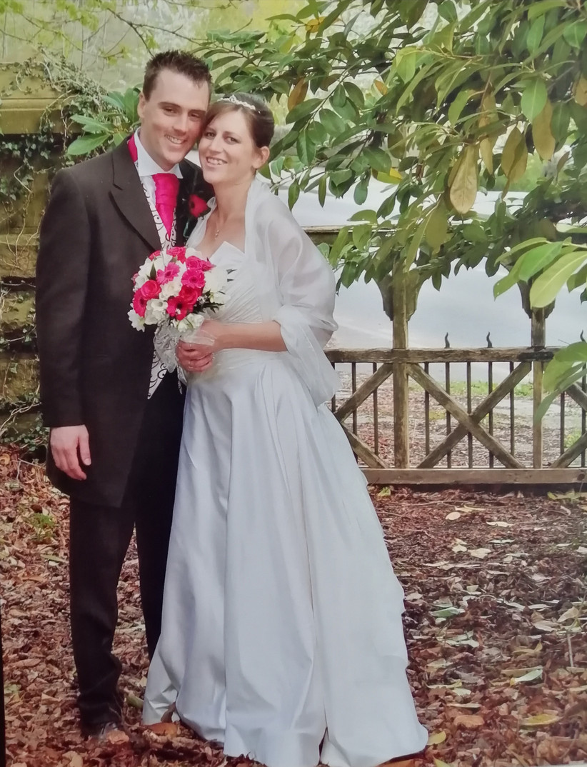 Portrait of a white newlywed couple with the bride in a white wedding dress with a white shawl and pink and white bouquet and the groom in a dark grey tux with a waistcoat and bright pink tie