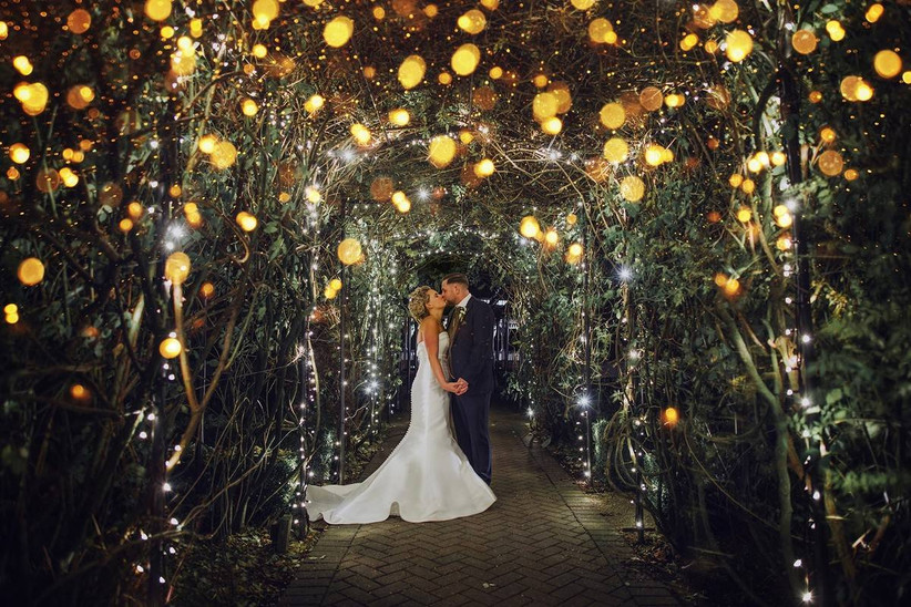 Bride and groom kiss under an archway of fairy lights
