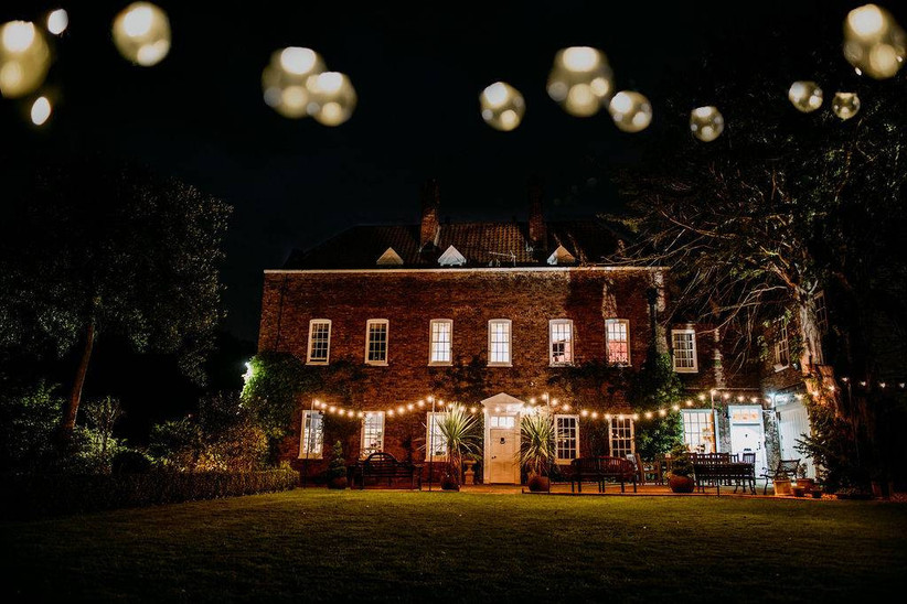 Outside view of a house at night lit up with lanterns