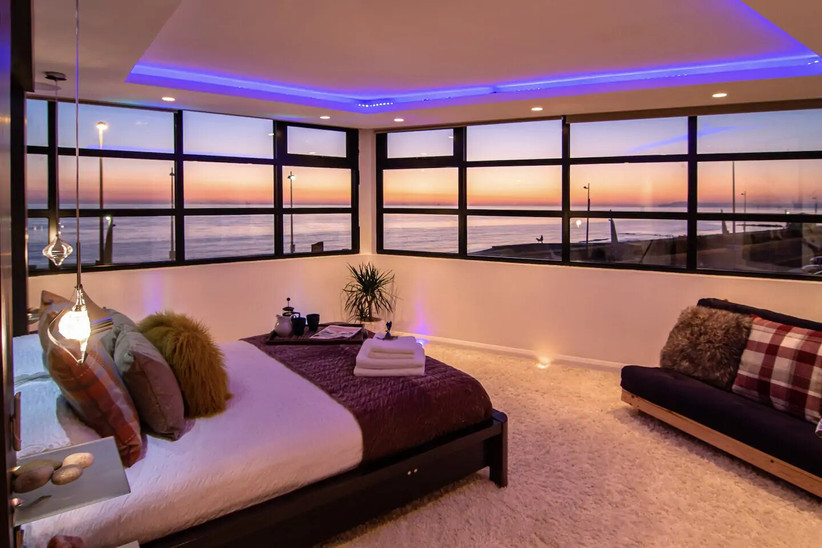 Bedroom with windows overlooking the sea at sunset