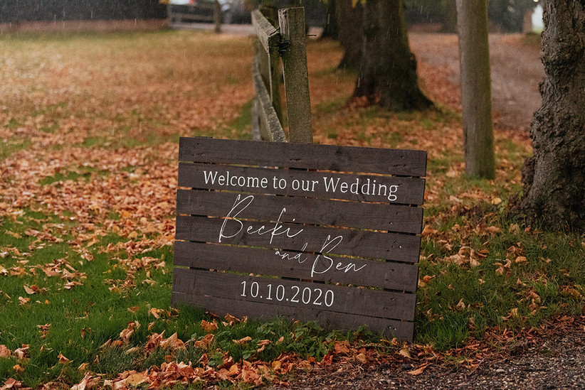 Wooden sign welcoming guests to Becky and Ben's wedding