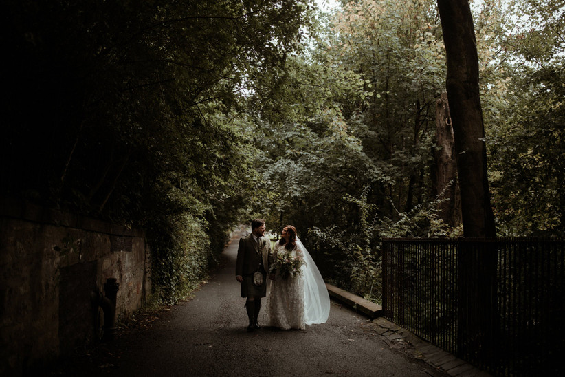 White newlyweds walking down a park path surrounded by green leaves with the groom wearing a green tweed suit and a kilt and the bride wearing a floral embroidered long-sleeved dress and white veil