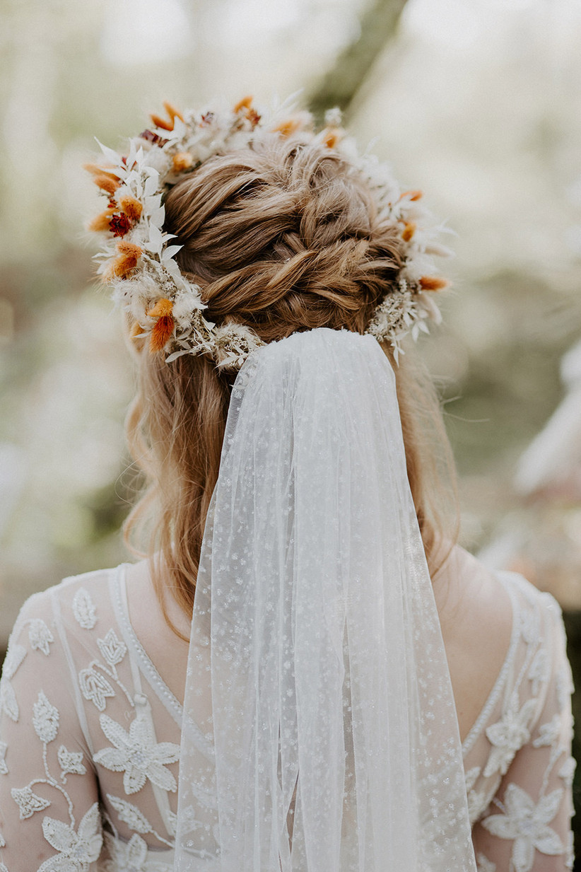 French braid hairstyle with autumnal flowers and a veil