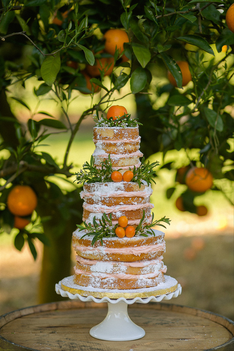 Three tiered naked rustic wedding cake with citrus fruits