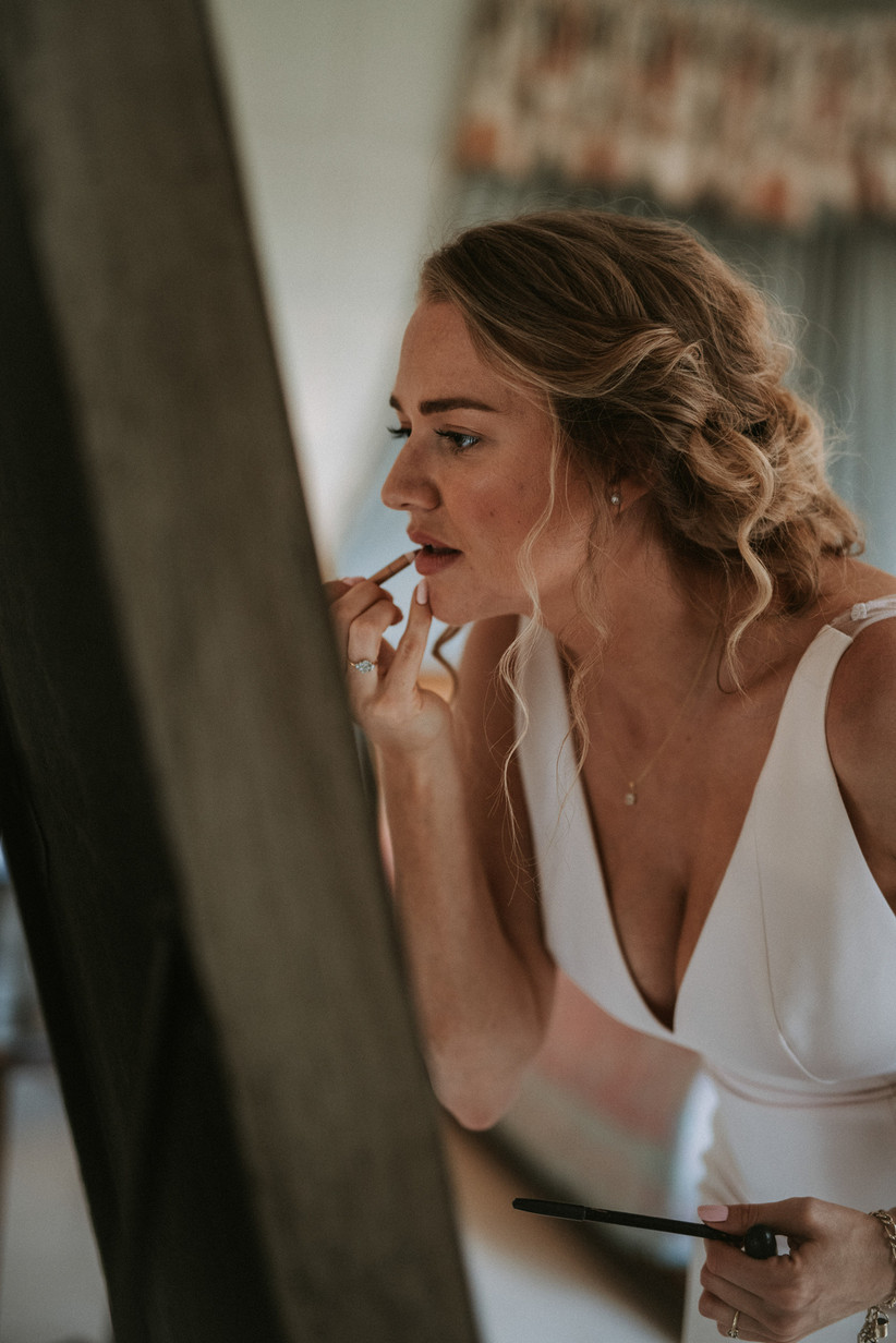 Katherine in her wedding dress applying lipstick in a mirror