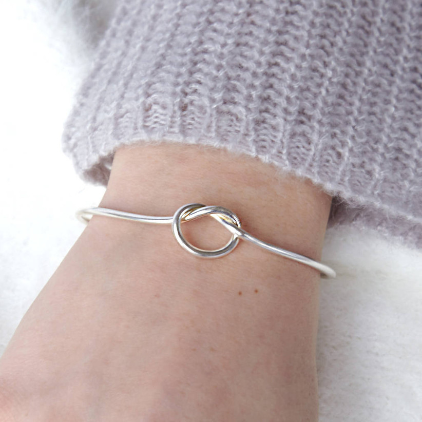 Close-up of a woman wearing a silver metal infinity knot bangle