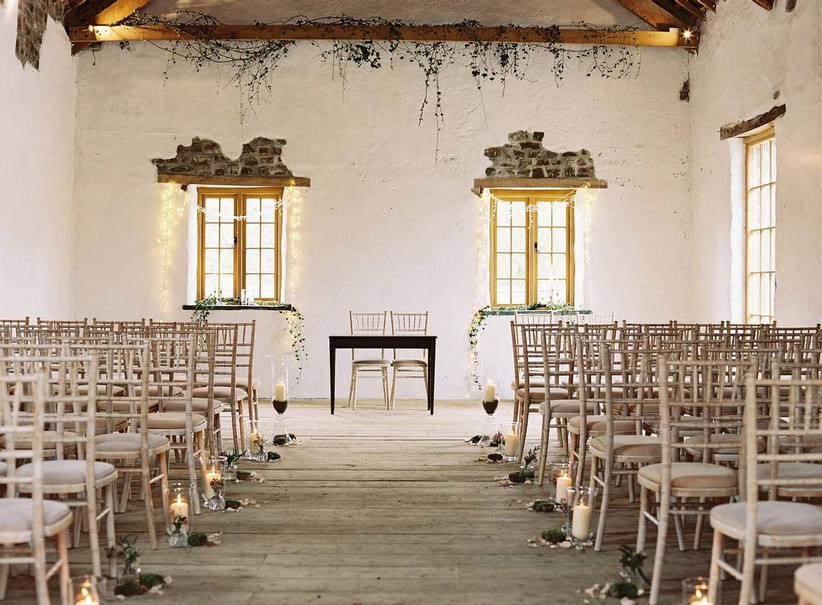 Rustic wedding ceremony with exposed walls and wooden chairs