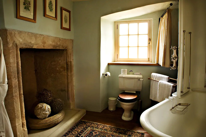 Bathroom with toilet, bath and large stone fireplace