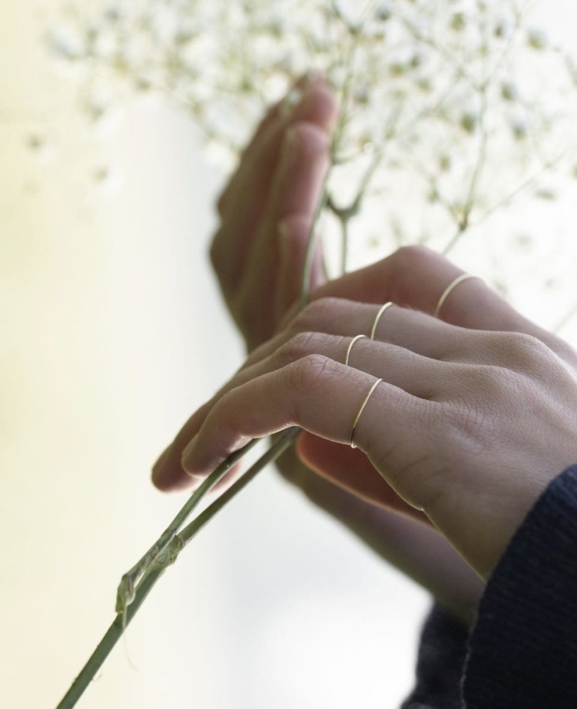 Woman holding a sprig of greenery wearing a wire thin gold band on each finger