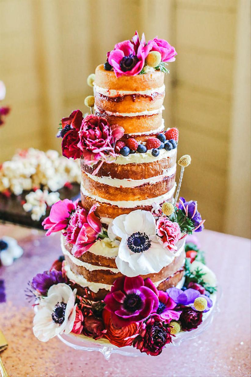 Three tiered victoria sponge rustic wedding cake with bright flowers