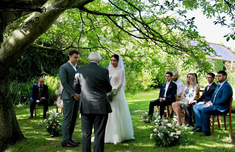 Couple at an outside wedding ceremony with guests watching