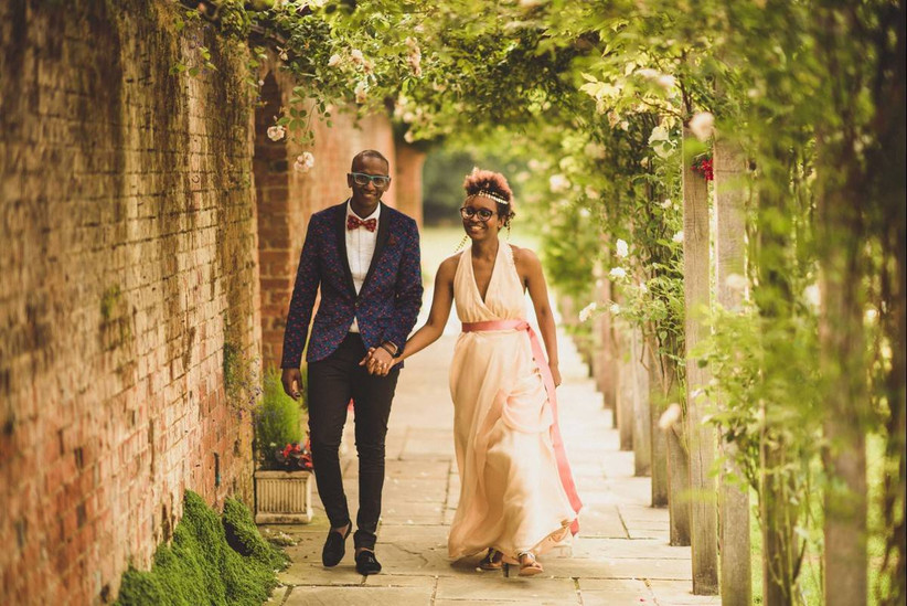 Bride and groom walking hand in hand in a rose covered archway