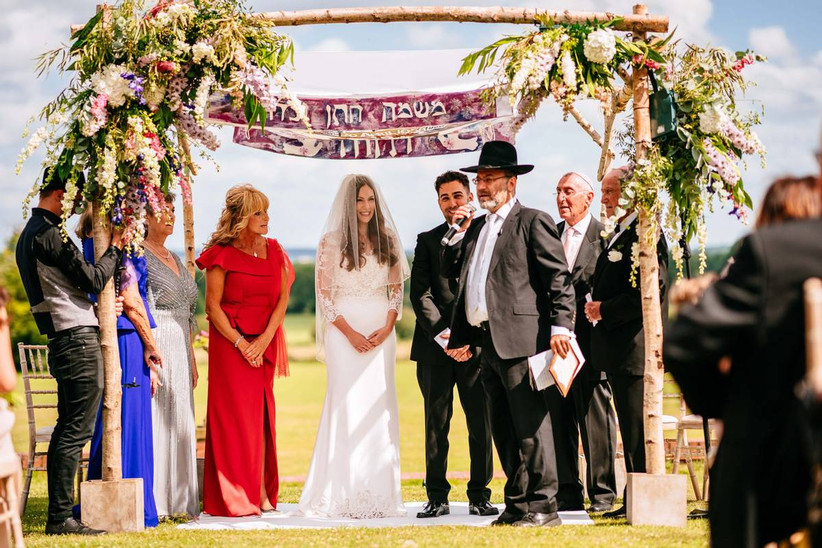 Bride, groom and guests under a wooden archway for a wedding ceremony