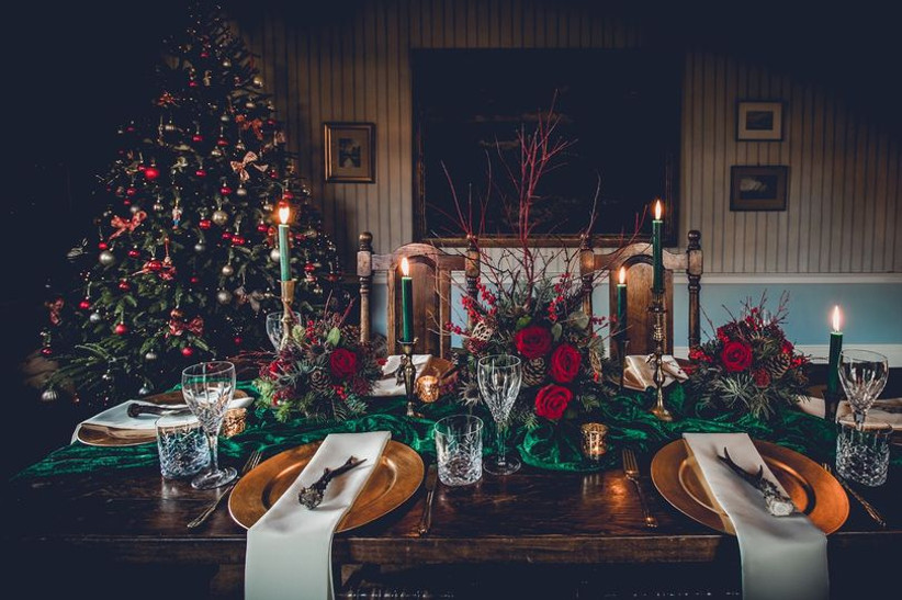 Dinging table decorated with candle sticks and festive foliage with a Christmas tree in the corner