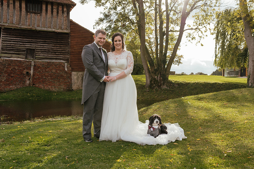 Becky and Ben in the garden with their dog lying on the train of Becky's wedding dress
