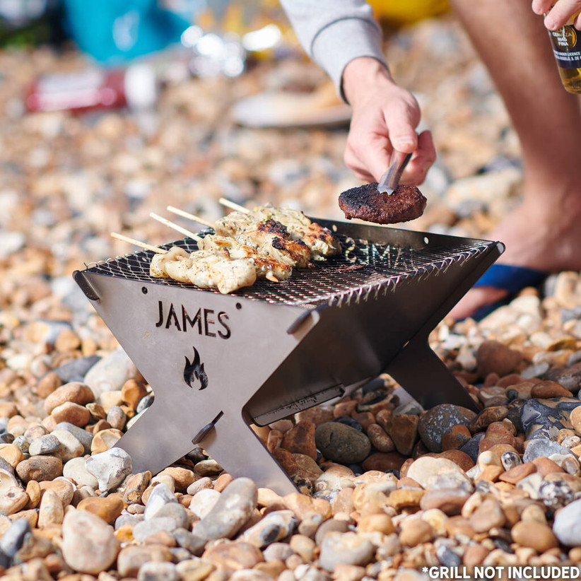 Man putting a burger onto personalised metal campfire that's cooking chicken kebabs