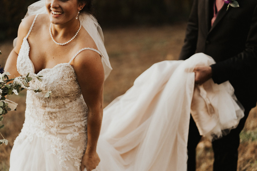 Bride in beaded scrappy wedding dress laughing with groom holding her train behind her