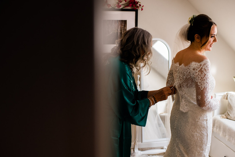 Caitlin's mum doing up her wedding dress