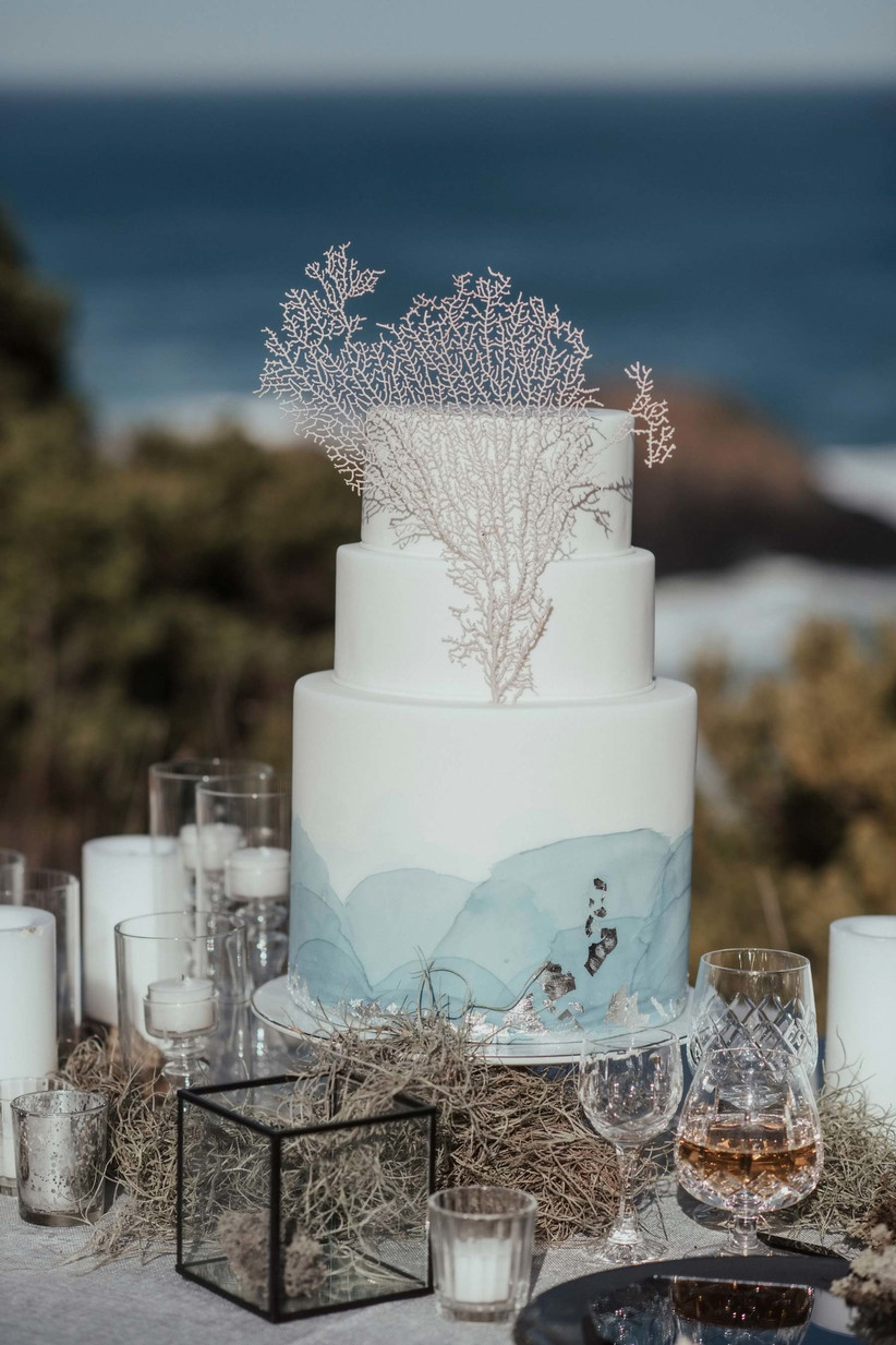 Three tiered white and blue fondant rustic wedding cake with coral