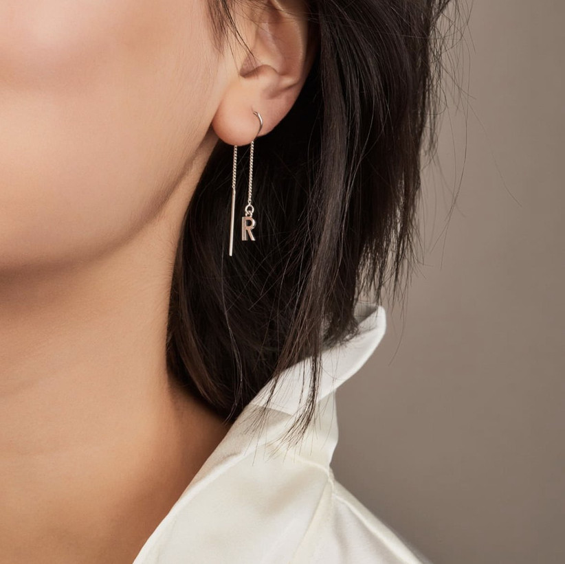 Woman wearing a white shirt and a single drop long chain silver earring with an R initial