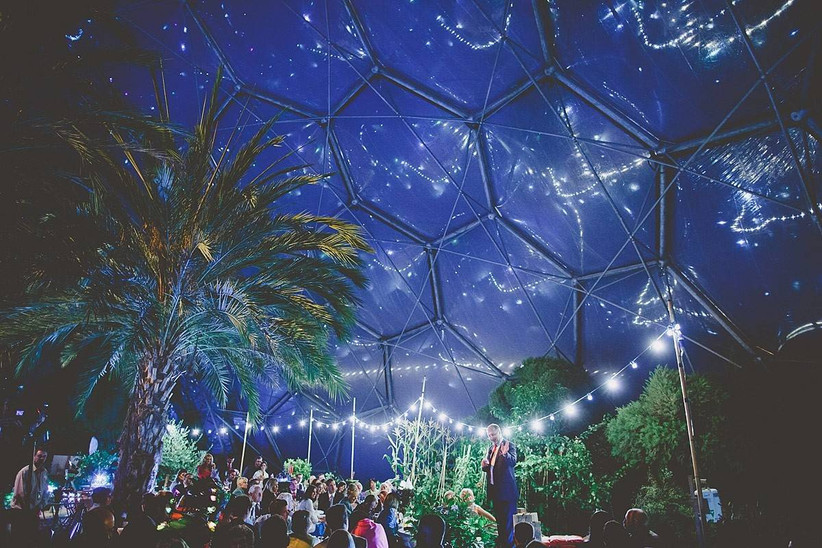 Man does a wedding speech at night inside the Eden Project Biome decorated with fairy lights