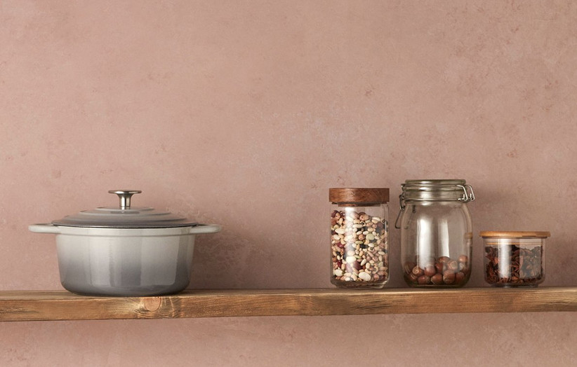 A grey cast iron casserole pot on a wooden shelf next to jars of dried beans against a pale pink wall