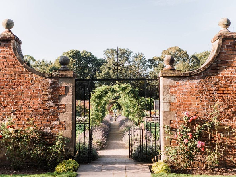 Metal gate and stone wall around a country garden