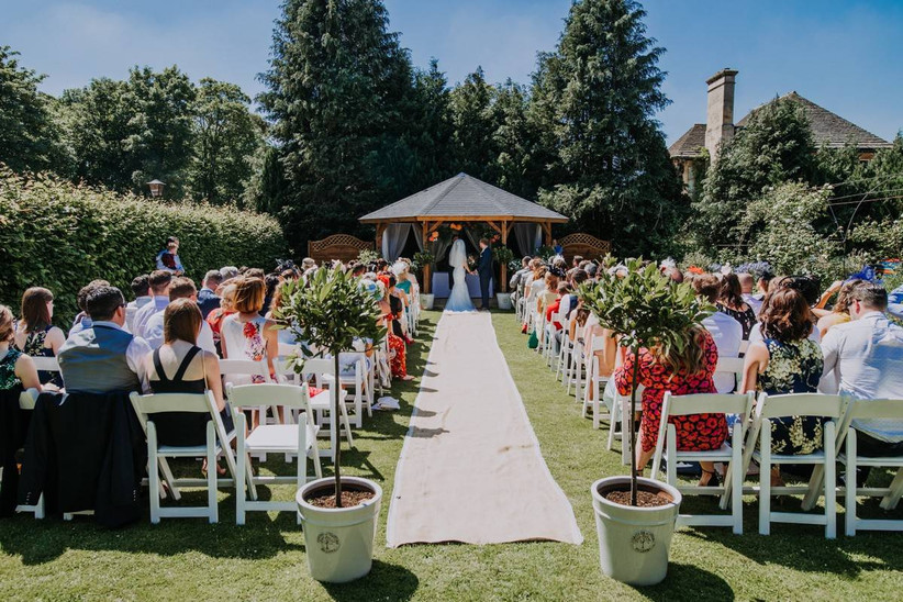Outside wedding ceremony on a sunny day with tree decorations