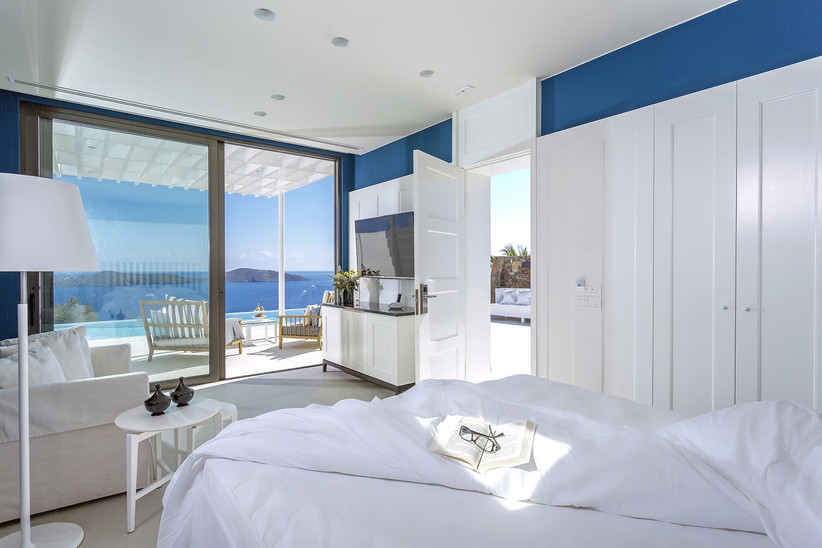 Beautiful blue and white villa bedroom with glass doors out into a pool