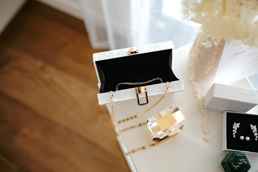 Hard box pearl clutch bag with a gold clasp and chain on a white table with perfumes, dried flowers and jewellery