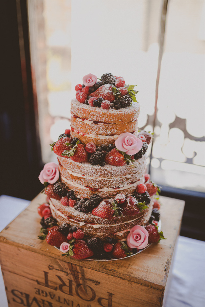 Three tiered naked victoria sponge rustic wedding cake with fruit