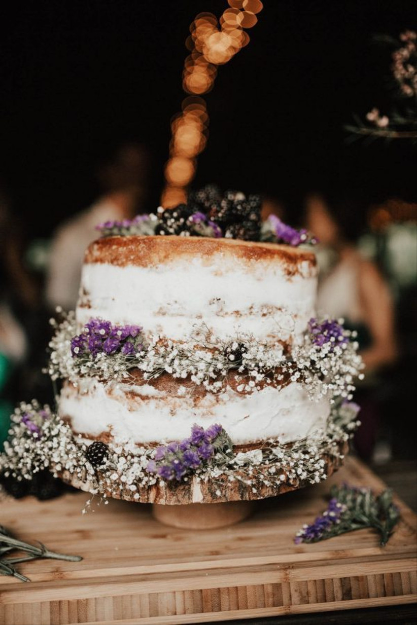 Two tiered semi naked rustic wedding cake with lavender and baby's breathe