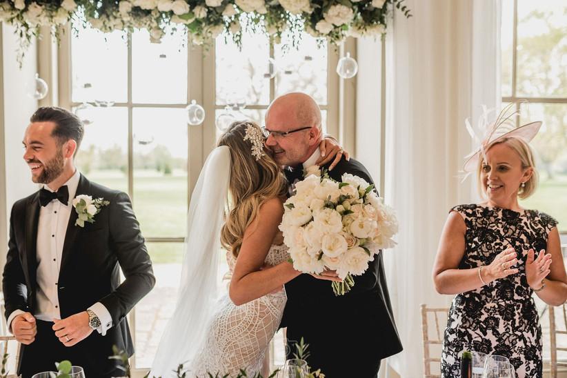 A bride hugging an older man in a suit