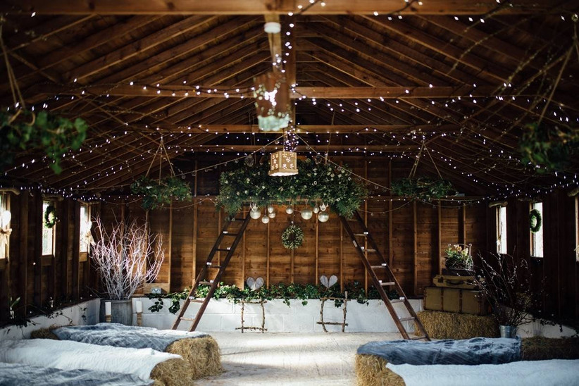 Rustic barn wedding ceremony with fairy lights and foliage