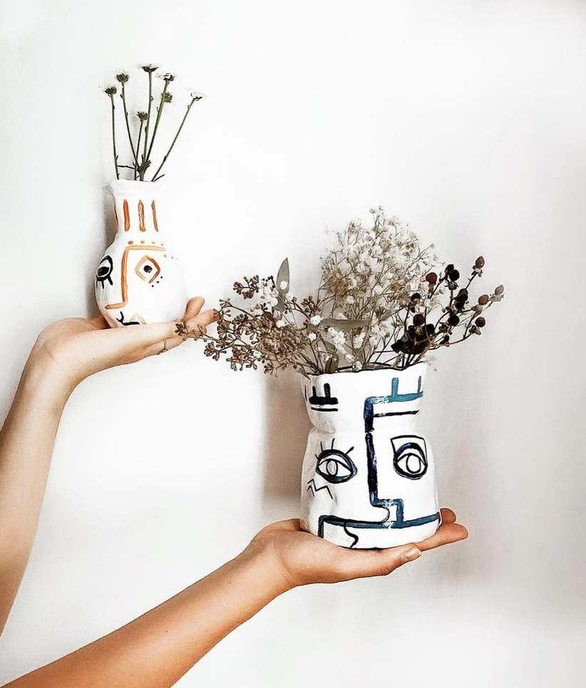 Woman holding a homemade clay pot in one hand and a homemade pottery vase containing dried flowers in the other