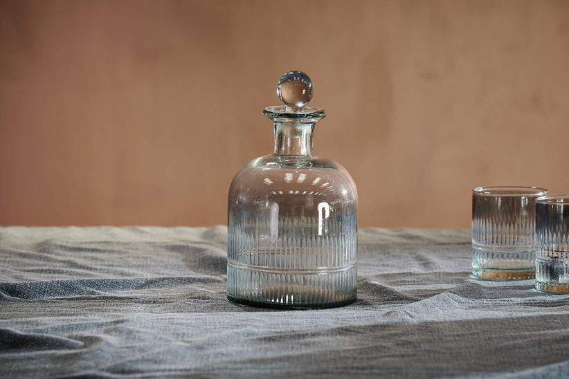 A smoked glass decanter on a pale blue linen tablecloth next to two smoked glass tumblers against a light brown wall