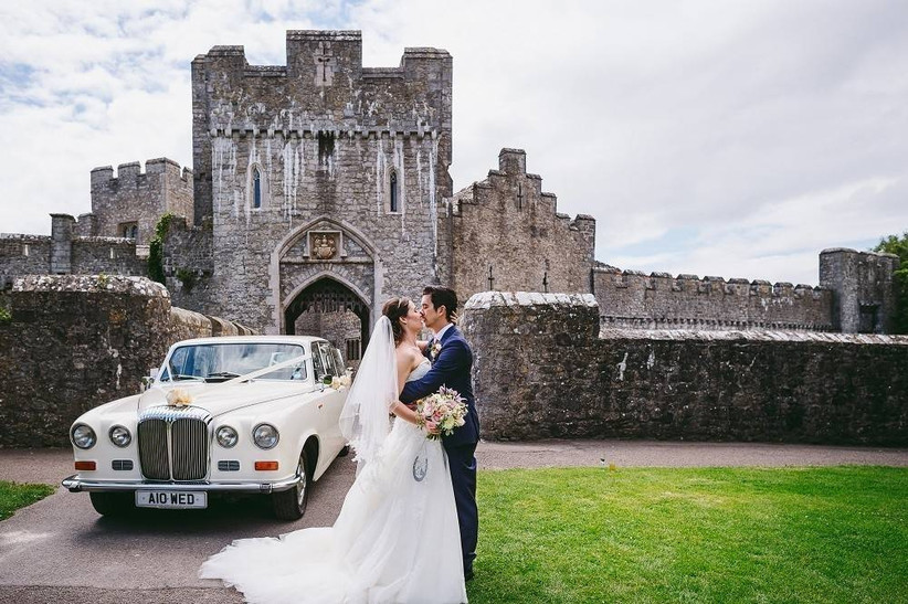 Bride and groom kiss standing next to a cream classic car outside a castle