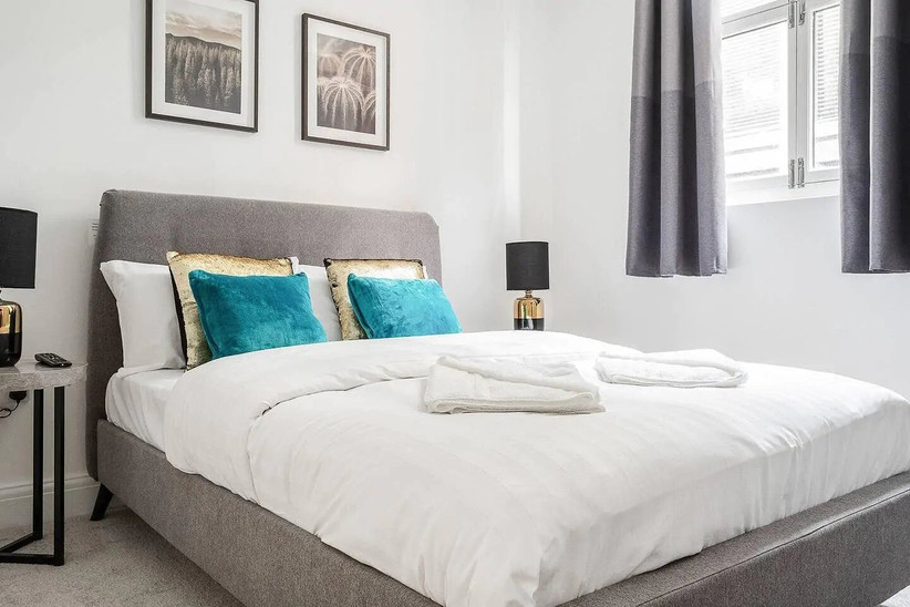 Double bed with gold and teal cushions