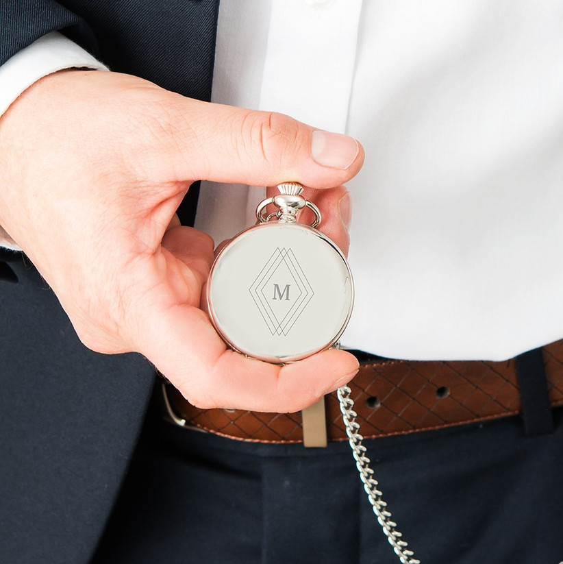 Man in a suit holding a silver Art Deco style pocket watch engraved with the initial M