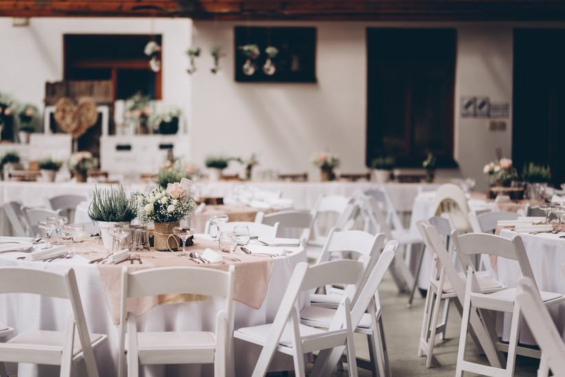 Empty rustic wedding venue with laid white tables, white chairs and pale pink tablecloths