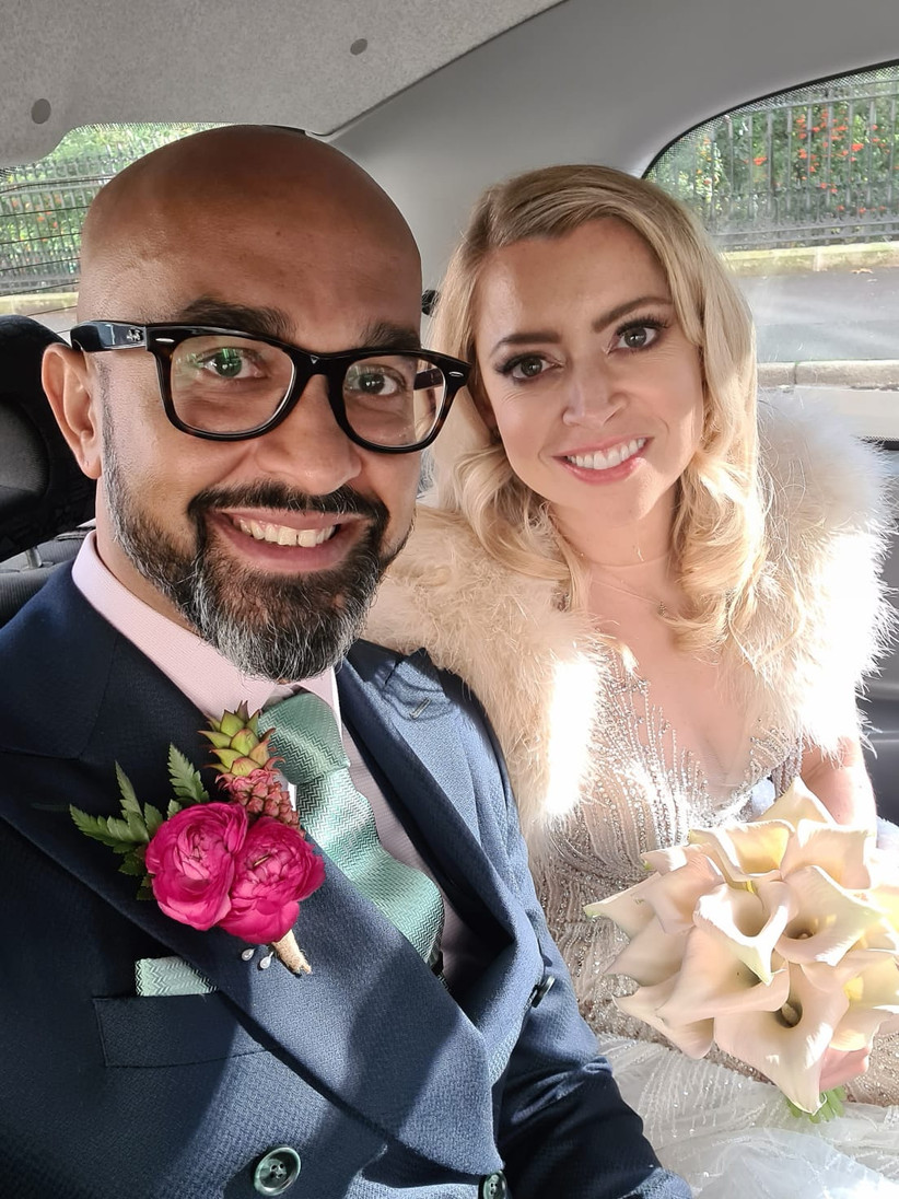 Selfie of a newlywed couple in the back of a wedding car with the brown-skinned groom wearing black rimmed glasses with a light pink shirt, bright pink buttonhole and dark suit and the blonde haired white bride wearing a beaded wedding gown and ivory fur cape