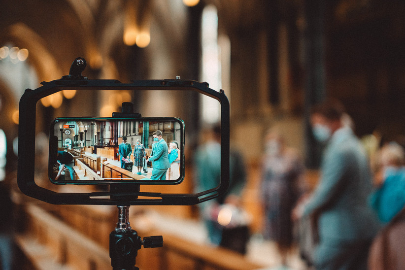 A mobile phone mounted on a stand filming a wedding ceremony in a church