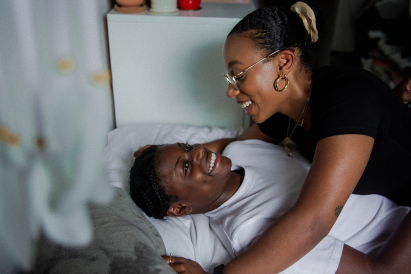 Two black women laughing together in bed during the day