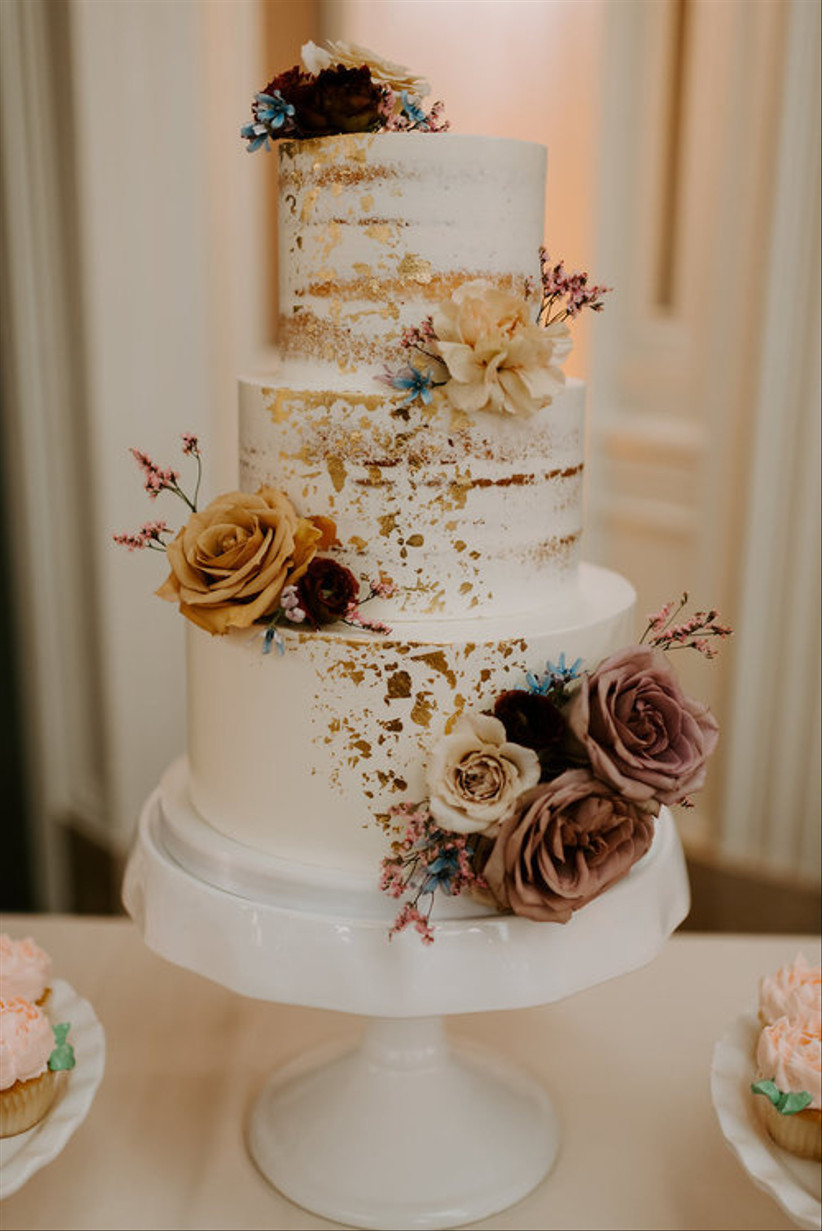 Three tiered white rustic wedding cake with metallic gold leaf and flowers