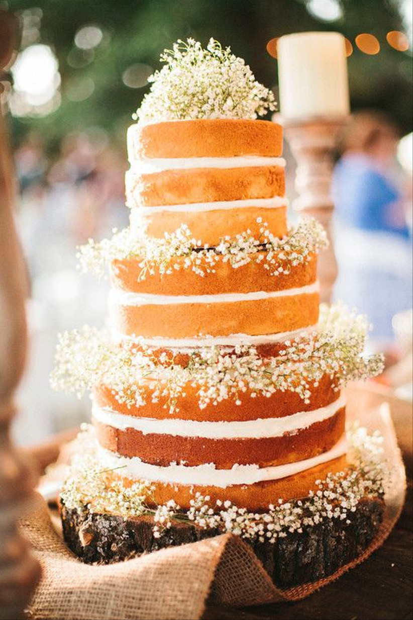 Three tiered naked rustic wedding cake with baby's breathe