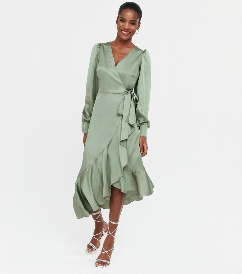 Girl wearing a sage green wrap dress with silver strappy heels